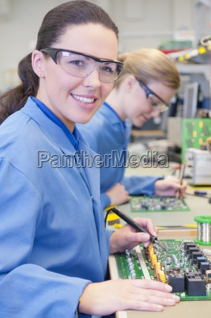 portrait of smiling technician soldering circuit