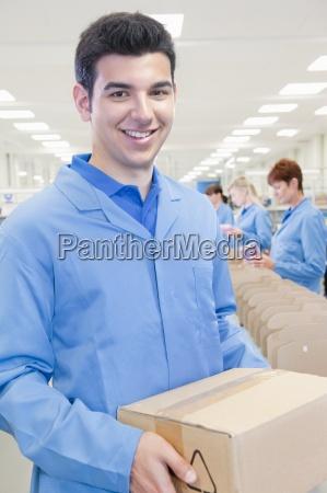 portrait of smiling worker holding cardboard