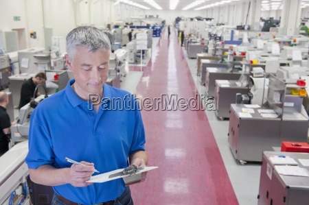 engineer with clipboard in aisle of