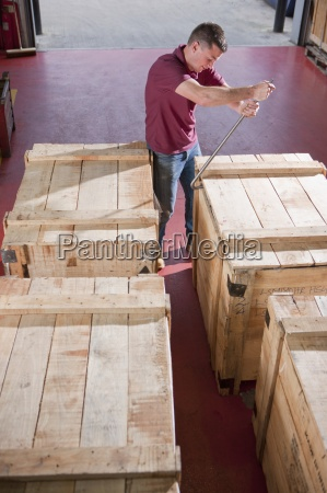 worker opening crate with crowbar in