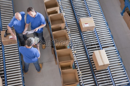 workers meeting among boxes on conveyor