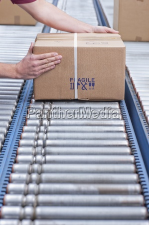 hands of worker packing box on