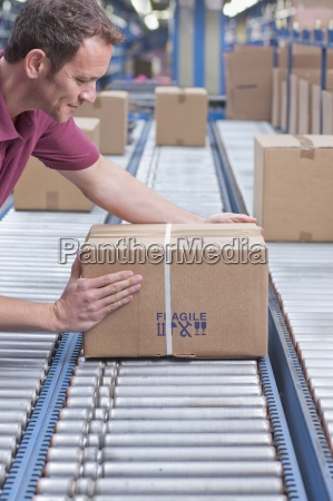 worker packing box on conveyor belt