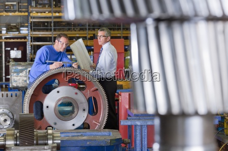 engineer and worker inspecting gear wheels