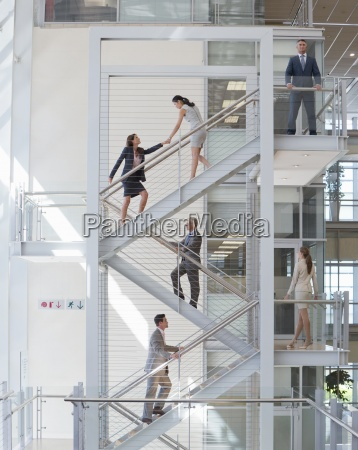 business people ascending stairs in office
