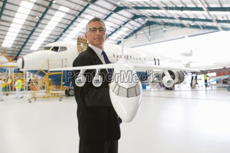 portrait of businessman holding model airplane