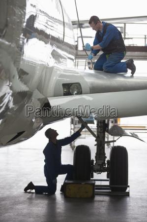 engineers repairing landing gear on passenger