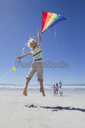 boy jumping and reaching for kite