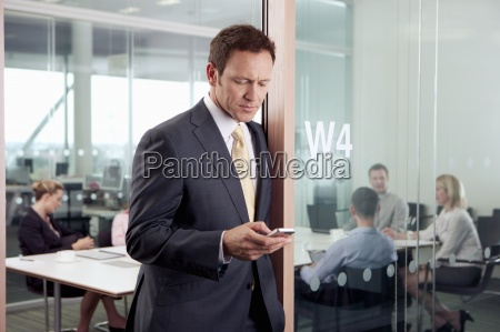 serious businessman text messaging on cell