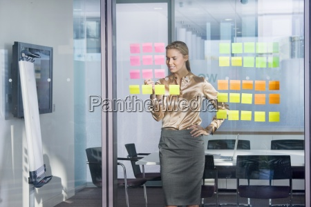 smiling businesswoman looking at adhesive notes
