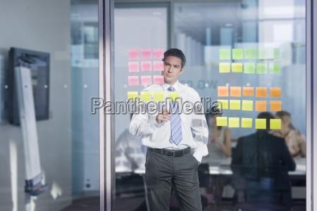 pensive businessman looking at adhesive notes