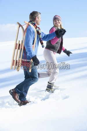 happy couple with sled walking and