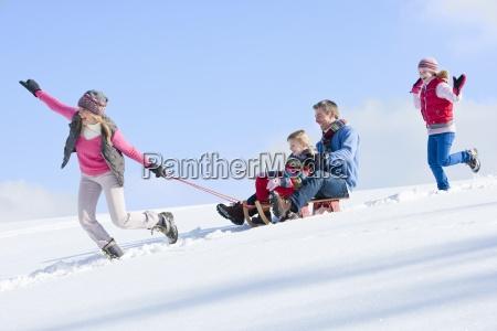 feliz familia trineo abajo nevoso colina