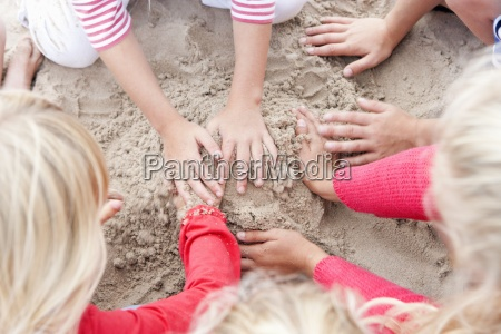 hands of kids making sandcastle on