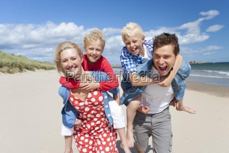 portrait of smiling parents piggybacking son