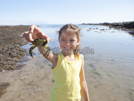 smiling girl holding small crab on