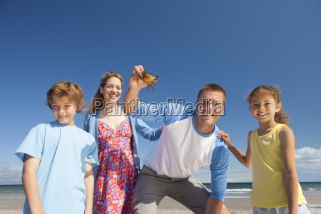 portrait of smiling family holding small