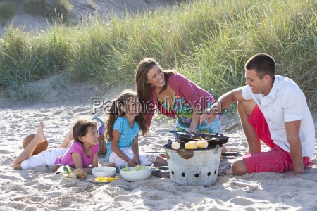 family with barbecue on beach