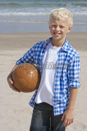 portrait of smiling boy holding soccer