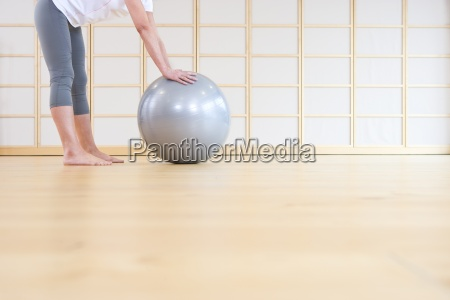 barefoot woman leaning against fitness ball