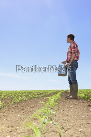 farmer with watering can in field