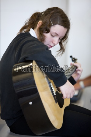 girl practicing guitar