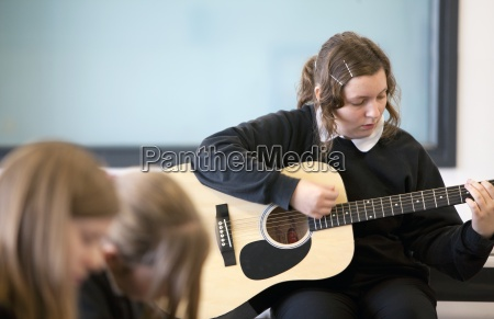 girl practicing guitar in classroom