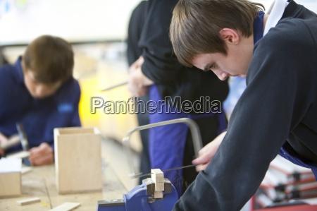 boy using saw to cut wood