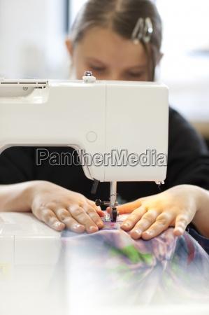 girl using sewing machine in school