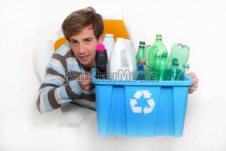 young man holding a recycling bin