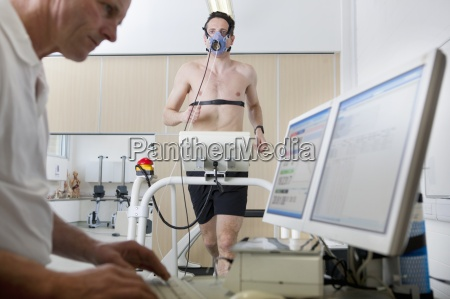 sports scientist at computer and runner