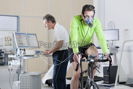 sports scientist at computer and cyclist