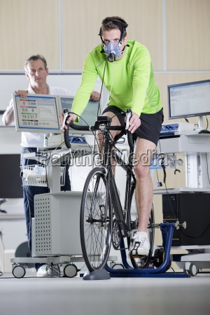 sports scientist monitoring cyclist with mask