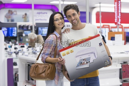 portrait of smiling couple holding printer