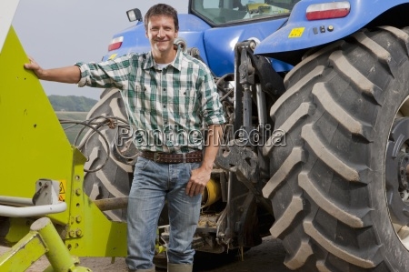 farmer attaching farm equipment to tractor