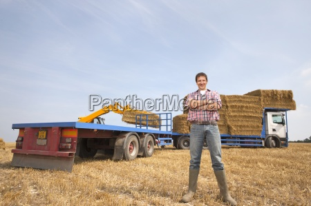 farmer supervising straw bales being loaded