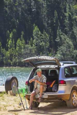 man preparing fishing rod at back