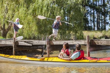 parents in kayaks on lake watching