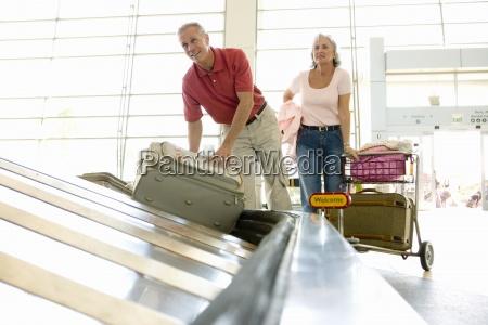 senior man retrieving suitcase from luggage