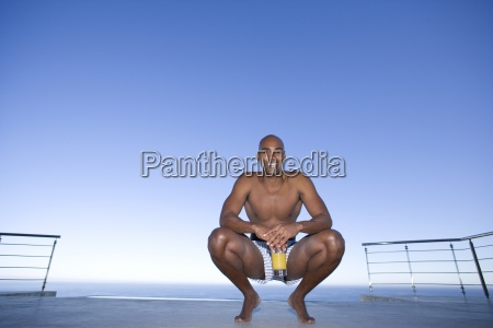 young man crouching on ground by