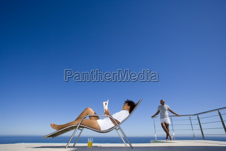 young woman reading on deck chair