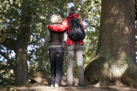 a mature couple standing in woodland