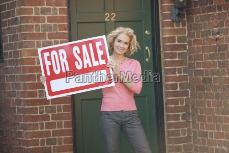 a mature woman holding a property