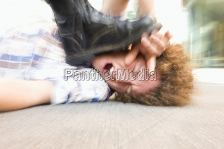 young man lying on ground being