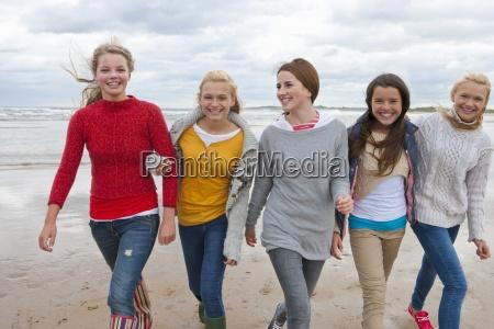 portrait of teenage girls walking arm