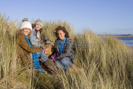 friends sitting on sand dune near