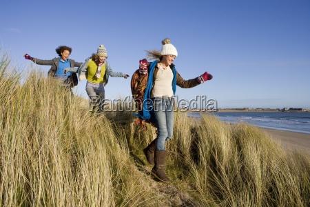 friends walking on sand dune near