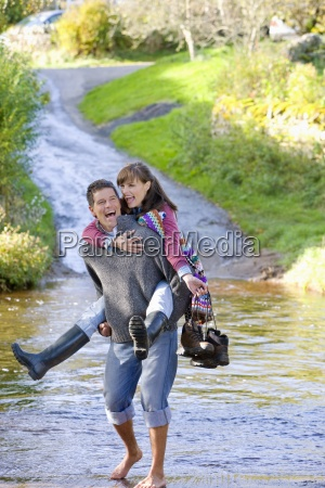 laughing husband carrying wife through shallow