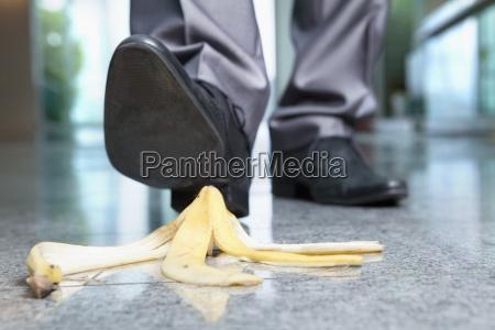 businessman stepping on banana peel