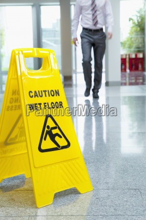 businessman approaching wet floor sign on